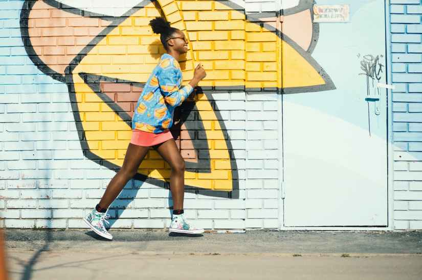 woman wearing blue and yellow long sleeved shirt walking near white and yellow painted wall